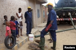 FILE - Sanitation workers removes septic waste from a house in Guediawaye, Senegal, Aug. 19, 2015. Government, charitable organizations are installing new toilets that turn waste into compost or break down matter with worms in bid to lower health risks.