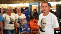 Russian tourists wearing t-shirts bearing a portrait of Russian President Vladimir Putin, queue inside the airport in Egypt's Red Sea resort of Sharm El-Sheikh on Nov. 6, 2015. Russia has halted all flights to Egypt. AFP PHOTO / MOHAMMED EL-SHAHED