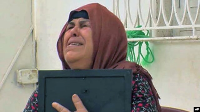 Umm Zine Nceri, the mother of 36-year-old Adel Hammami, who threatened to expose fraud within Tunisia's old ruling RCD party and was brutally killed, cries as she holds a photo of Hammami, in Sidi Bouzid, Tunisia, August 2011
