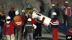Rescue workers and officials maneuver the capsule that will be used to extract 33 trapped miners one by one from the collapsed San Jose Mine near Copiapo, Chile, 12 Oct. 2010