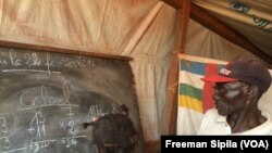 Un enseignant interroge son élève au tableau dans une école de fortune sur le site des déplacés de PK3 Bria, février 2017. (VOA/Freeman Sipila)