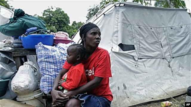 A woman displaced due to the Jan 12, 2010 earthquake holds a child as she rests next to her tent and belongings before leaving the refugee camp at the Saint Pierre park in Port-au-Prince, Haiti, Dec 14, 2010