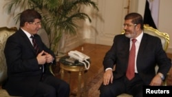FILE - Former Egyptian President Mohamed Morsi (R) meets with Turkey's Foreign Minister Ahmet Davutoglu at the presidential palace in Cairo, Sept. 17, 2012.