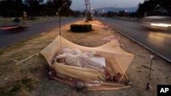在巴基斯坦伊斯蘭堡,打短工的人睡在公路中央的蚊帳內。(資料照)