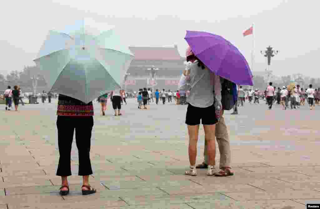 Visitors to Tiananmen Square shield themselves from the sun with umbrellas on a hot and hazy day, July 28, 2010.