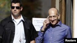 Former Israeli Prime Minister Ehud Olmert (R) speaks on the phone as he leaves the Jerusalem District court, September 24, 2012.