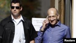 Former Israeli Prime Minister Ehud Olmert (R) speaks on the phone as he leaves the Jerusalem District court, September 24, 2012.