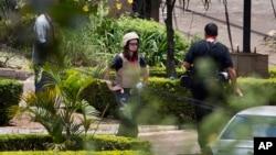 Una extranjera no identificada involucrada en la investigación forense inspecciona la escena frente al centro comercial Westgate en Nairobi.