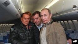 ປະທານາທິບໍດີ Dmitry Medvedev (ເຄິ່ງກາງ) ທ່ານນາຍົກ Vladimir Putin (ຂວາ) ທ່ານນາຍົກລັດຖະ ມົນຕີອີຕາລີ Silvio Berlusconi (ຊ້າຍ) ພາກັນຖ່າຍຮູບຮ່ວມກັນໃນຂະນະທີ່ໄປ ກວດເບິ່ງເຮືອບິນໂດຍສານ ໃໝ່ Sukhoi Superjet 100, ທີູ່ຄຸ້ມບ້ານພັກ Sochi ແຄມທີ່ທະເລດຳໃນພາກ ໃຕ້ຂອງຣັດເຊຍໃນ
