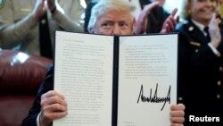 特朗普總統在白宮橢圓形辦公室展示他否決的國會決議。(2019年3月15日)