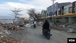 Warga melintas dengan sepeda motor di antara puing-puing dari bekas bangunan yang rusak akibat gempa bumi dan terjangan tsunami di pantai teluk Palu (24/11) Foto: VOA/Yoanes Litha