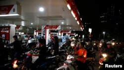 Para pengendara motor antri untuk mengisi bensin di stasiun pengisian bahan bakar milik Pertamina di Jakarta, Indonesia, 17 November 2014.