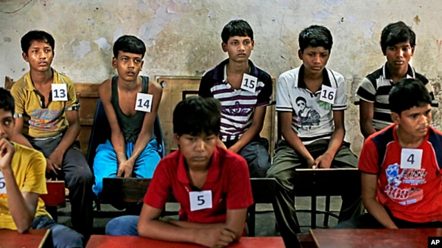 Young Indian bonded child laborers wait to be processed at a safe house after being rescued during a raid by workers from Bachpan Bachao Andolan, or Save the Childhood Movement, at a  factory in New Delhi, India,  June 11, 2013.