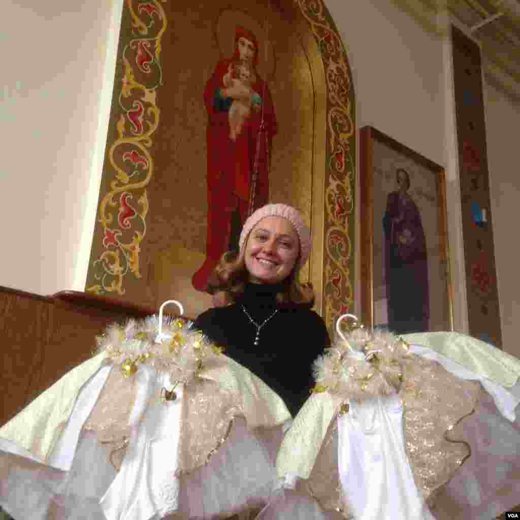 Choir Director Zlata Mishima, a recent Russian immigrant, holds the costumes for the Snow Queen portion of the Christmas Pageant. (Adam Phillips/VOA)