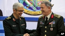 Kepala angkatan bersenjata Turki, Jenderal Hulusi Akar (kanan) diterima Panglima militer Iran Jenderal Mohammad Hossein Bagheri, di Teheran, Senin (2/10).