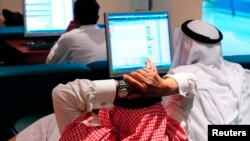 FILE - Traders monitor stocks at the Saudi Hollandi Bank in Dammam, 350 km (217 miles) east of Riyadh, March 28, 2011.