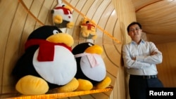 FILE - Tencent Chairman and CEO Pony Ma poses with mascots for QQ.com in 2011. Two chatbots, BabyQ and XiaoBing, on Tencent's messaging service, QQ were taken offline after making politically sensitive remarks. (Reuters/Bobby Yip)