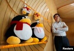 2011年6月9日,腾讯董事长兼首席执行官马化腾在深圳南山高科技工业园区的公司总部内接受路透社采访,旁边是腾讯网的吉祥物。