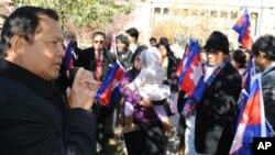 Cambodia's Ambassador to Washington DC, Hem Heng, far left, joins in to celebrate the flag ceremony in Philadelphia.