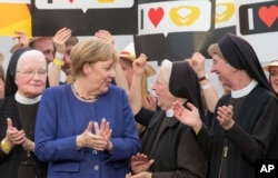 German Chancellor and top candidate of the Christian Democratic, Angela Merkel gains support from nuns during a campaign appearance in Delbrueck, Sept. 10, 2017.