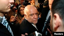Iranian Oil Minister Bijan Zanganeh is surrounded by journalists and security staff as he arrives at his hotel ahead of an OPEC meeting in Vienna, Dec. 3, 2013.