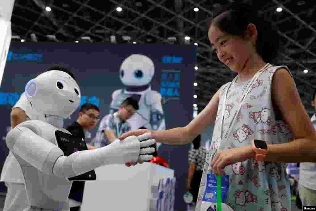 دست دادن یک بازدیدکننده با ربات انسان نما در نمایشگاه بین المللی ربات در شانگهای چین