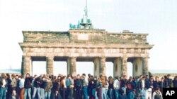 Berlin, 10 noyabr 1989-cu il -Şərqi və Qərbi almanlar Brandenburq qapısı qarşısında Berlin divarı üzərində dayanıb.