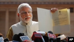 India's next Prime Minister and Hindu nationalist Bharatiya Janata Party (BJP) leader Narendra Modi displays the letter from the President inviting him to form the new government, outside the Presidential Palace in New Delhi, May 20, 2014.