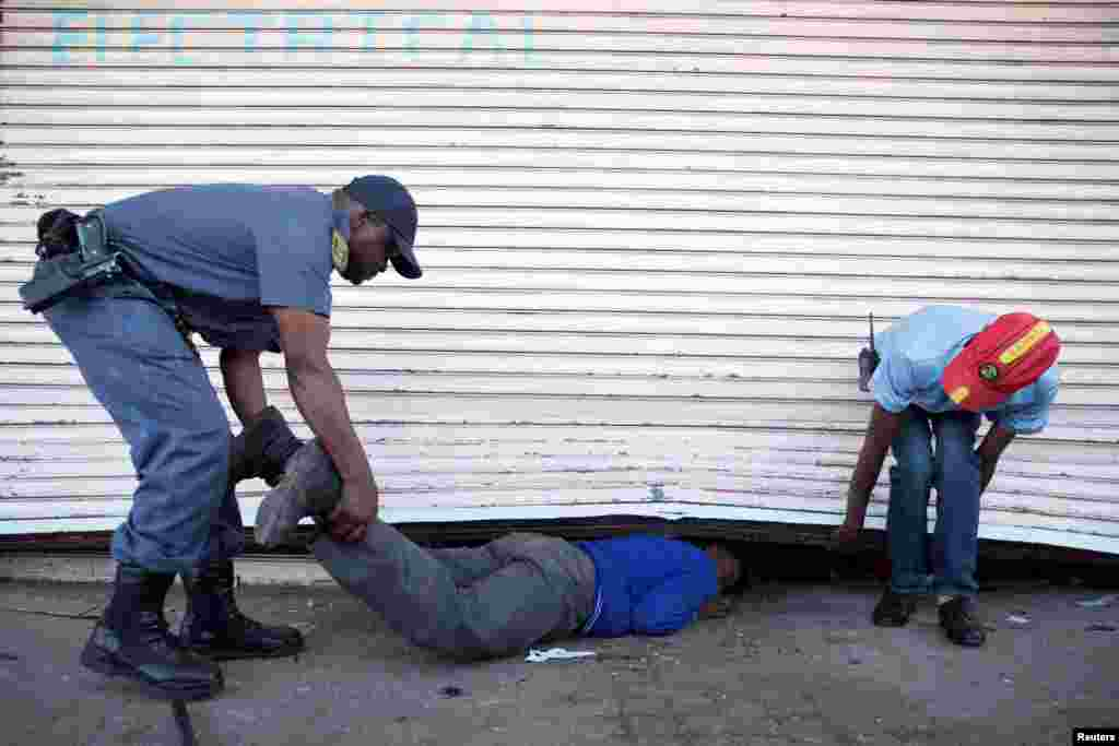 Police arrest a school pupil for looting in the South African township of Soweto, where foreign shop owners were attacked and at least two were killed, Aug. 29, 2018.