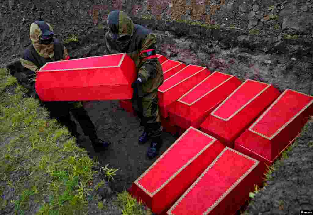 Men place coffins with the remains of Red Army soldiers killed in World War II in a grave during a reburial ceremony ahead of Victory Day celebrations in Kaliningrad, Russia.