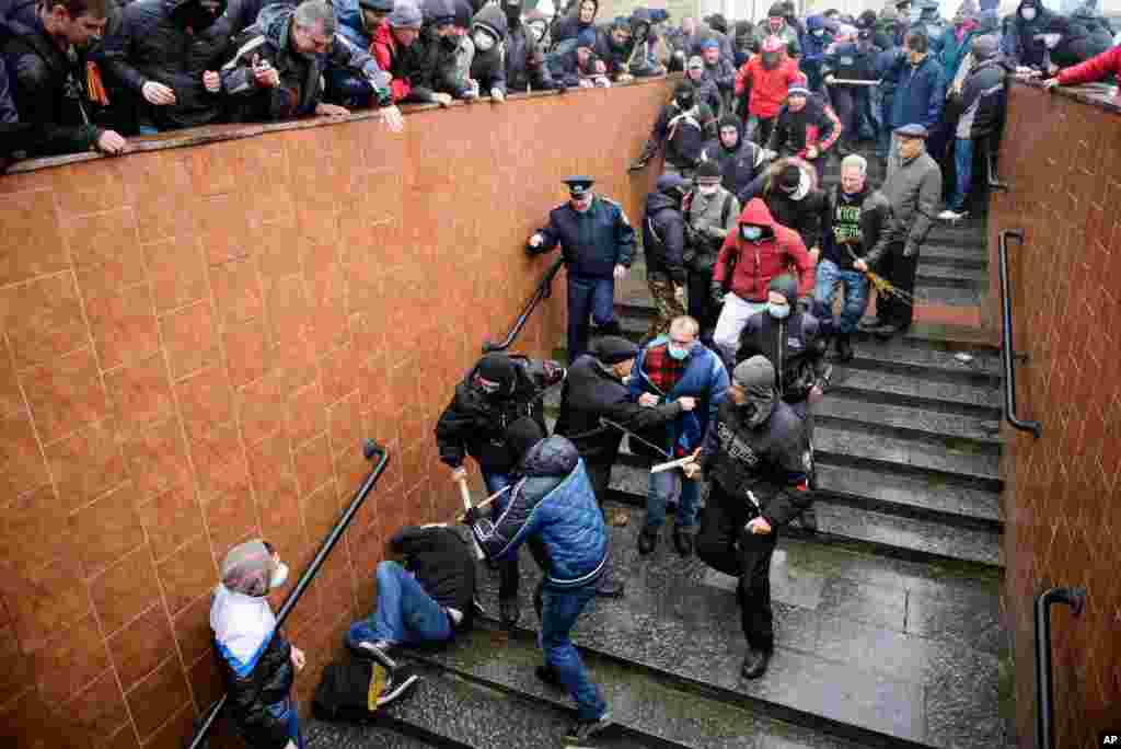 Pro-Russia supporters beat a pro-Western activist during a pro-Russian rally in Kharkiv, Ukraine, April 13, 2014.