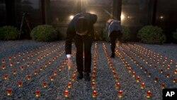 중국에서 난징대학살 사건이 처음 국가추모일로 제정된 가운데 13일 추모식을 앞두고 행사 요원들이 초에 불을 붙이고 있다.