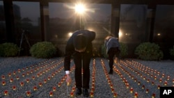 Chinese workers light candles before a vigil to mark China's first National Memorial Day at the Nanjing Massacre Memorial Hall in Nanjing in eastern China's Jiangsu province on Saturday, Dec. 13, 2014.