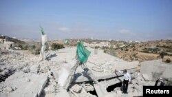 Bendera Hamas berkibar di atas puing-puing rumah Hussam Kawasme, salah seorang warga Palestina yang dicurigai menculik dan membunuh tiga remaja Israel pada Juni di kota Hebron, Tepi Barat (18/8).