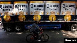 A man cycles past a truck of Corona beer produced by Group Modelo in Mexico City July 16, 2013.