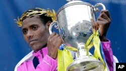 Lelisa Desisa, of Ethiopia, lifts his trophy after winning the Boston Marathon, Monday, April 20, 2015 in Boston. (AP Photo/Elise Amendola)