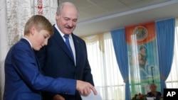 ປະທານາທິບໍດີ ເບລາຣູສ໌ ທ່ານ ລູຄາເຊັນໂກ ກັບລູກຊາຍຫຼ້າ ປ່ອນບັດລົງຄະແນນສຽງທີ່ໜ່ວຍເລືອກຕັ້ງ ໃນລະຫວ່າງການລົງຄະແນນສຽງເລືອກເເອົາປະທານາທິບໍດີ ທີ່ນະຄອນຫຼວງ Minsk, ປະເທດ ເບລາຣຸສ໌, 11 ຕຸລາ, 2015.