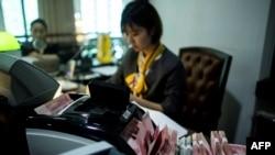 2018年8月8日在上海的一家銀行,員工使用點鈔機點算100元(相當於14.6美元)的鈔票。
