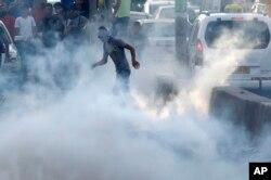23일 예루살렘과 서안지구 라말라를 잇는 검문소에서 팔레스타인 시위대가 이스라엘 진압병력이 터뜨린 최루가스 속에 서있다.