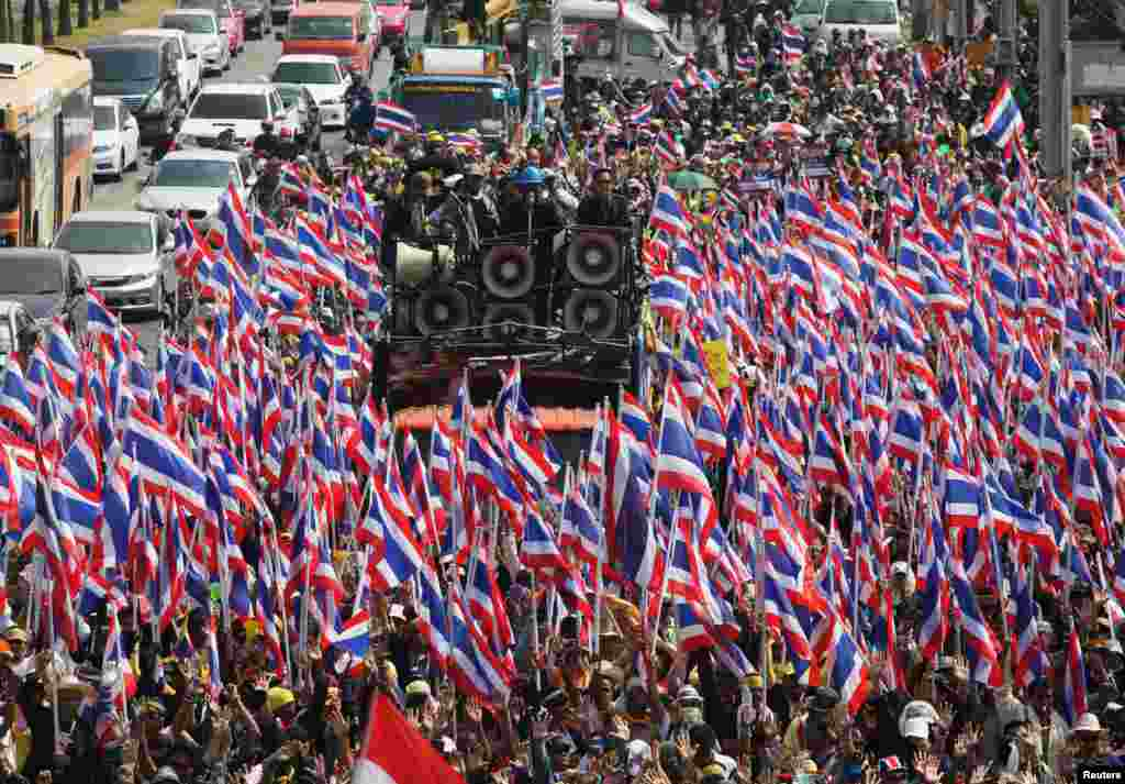 Anti-government protesters hold Thai national flags as they march towards the Department of Special Investigation (DSI) in Bangkok. The Thai baht plumbed its lowest level in almost four years as a political crisis grew more intractable.