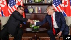 지난달 12일 도널드 트럼프 미국 대통령과 김정은 북한 국무위원장이 싱가포르 카펠라 호텔의 단독회담장에 입장한 후 다시 악수를 하고 있다. 두 정상은 사진 촬영 후 비공개로 회담을 진행했다.