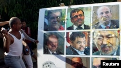 An anti-government protester throws an egg at a poster of Tunisian politicians, including Prime Minister Ali Larayedh (top row, C) and leader of the Islamist Ennahda movement Rached Ghannouchi (center row, R) in Tunis, Oct. 2, 2013.