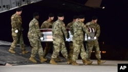In this image provided by the U.S. Air Force, a U.S. Army carry team transfers the remains of Army Staff Sgt. Dustin Wright of Lyons, Georgia, Oct. 5, 2017, upon arrival at Dover Air Force Base, Delware. Wright, 29, was one of four U.S. troops and four Niger forces killed in an ambush by dozens of Islamic extremists.