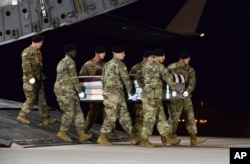 In this image provided by the U.S. Air Force, a U.S. Army carry team transfers the remains of Army Staff Sgt. Dustin Wright of Lyons, Georgia, Oct. 5, 2017, upon arrival at Dover Air Force Base, Delware. Wright, 29, was one of four U.S. troops and four N
