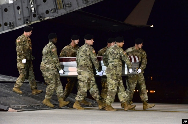 FILE - In this image provided by the U.S. Air Force, a U.S. Army carry team transfers the remains of Army Staff Sgt. Dustin Wright of Lyons, Ga., upon arrival at Dover Air Force Base, Del., Oct. 5, 2017. Four U.S. troops and four Niger forces were killed in an ambush by dozens of Islamic extremists in Niger.