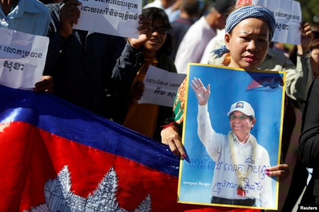 FILE - Supporters of Kem Sokha, leader of the Cambodia National Rescue Party, stand outside the Appeal Court during a bail hearing for the jailed opposition leader in Phnom Penh, Cambodia, Sept. 26, 2017.