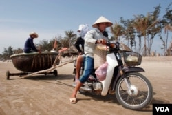 FILE - A motorbike is used to transport people and pull a fishing boat in Vung Tau. (Hai Do)