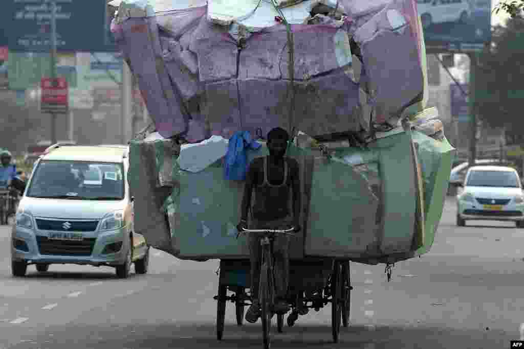 A laborer transports a large load of non bio-degradable waste on the outskirts of New Delhi, India.