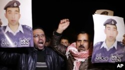People from the al-Kaseasbeh tribe and other tribes take part in a demonstration outside of Jordan's cabinet in Amman calling for the release of Jordanian pilot Lt. Mu'ath al-Kaseasbeh, who is held by Islamic State group militants, Jan. 27, 2015.