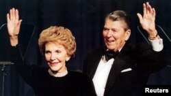 FILE - Former U.S. president Ronald Reagan and his wife Nancy wave while attending a gala celebrating his 83rd birthday, Feb. 3, 1994, in Washington.
